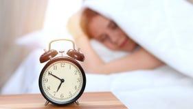 困年轻女人闹钟对面  早早醒,没得到足够睡眠概念 库存图片