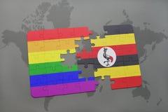 困惑与乌干达的国旗和在世界地图背景的快乐彩虹旗子 免版税库存照片