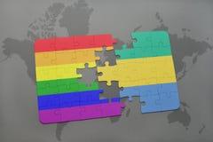 困惑与加蓬的国旗和在世界地图背景的快乐彩虹旗子 免版税库存图片