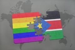 困惑与南苏丹的国旗和在世界地图背景的快乐彩虹旗子 免版税库存照片