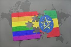 困惑与埃塞俄比亚的国旗和在世界地图背景的快乐彩虹旗子 免版税图库摄影