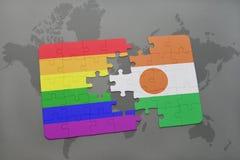 困惑与尼日尔的国旗和在世界地图背景的快乐彩虹旗子 免版税库存图片