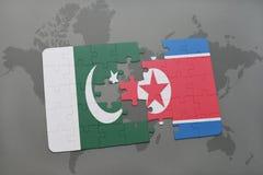 困惑与巴基斯坦和北朝鲜的国旗世界地图背景的 图库摄影