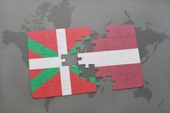 困惑与巴斯克国家和拉脱维亚的国旗世界地图背景的 库存照片