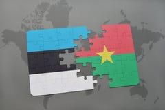 困惑与爱沙尼亚和布基纳法索国旗在世界地图 免版税库存照片
