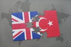 困惑与英国和土耳其国旗在世界地图背景 库存照片