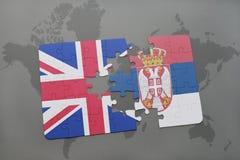 困惑与英国和塞尔维亚的国旗世界地图背景的 库存照片