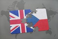 困惑与英国和捷克共和国国旗在世界地图背景 库存照片