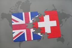 困惑与英国和瑞士的国旗世界地图背景的 库存照片