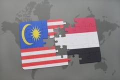 困惑与马来西亚和也门的国旗世界地图背景的 免版税库存图片