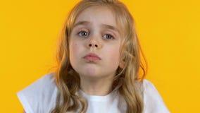 困惑的女孩耸肩的看,儿童伪善言辞做出决定,特写镜头 影视素材