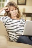 困惑的成熟妇女在家坐沙发使用膝上型计算机 库存照片