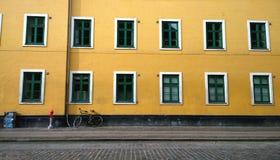 围住有许多的明亮的黄色房子美好的Windows 到倾斜自行车的墙壁 在一个小岗位附近 免版税库存照片