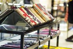围巾和披肩在商店窗口里 在时尚精品店的衣物 免版税库存图片