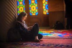围巾的少女坐一个地板在清真寺 免版税库存照片