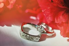 围拢与红色花,在金刚石头的特写镜头焦点的婚戒 免版税库存照片