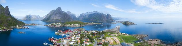围拢渔村和岩石峰顶雷讷,莫斯克内斯,罗弗敦群岛,挪威的蓝色海的美好的空中全景,晴朗 免版税库存照片