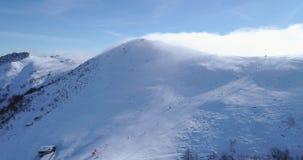 围绕在冬天多雪的山上面滑雪轨道的天线旋转依靠与滑雪者人滑雪 晴天,有雾的云彩 雾上升 股票视频