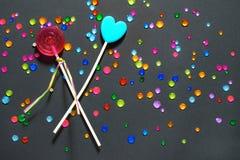 围绕红色和蓝色心脏的两个糖果棒棒糖在与多彩多姿的假钻石的黑背景 甜糖果概念 库存图片