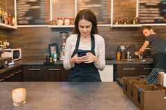 围裙咖啡馆工作者的年轻女人酒吧柜台的,接受在智能手机的命令 库存图片