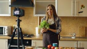 围裙射击录影食物博克的年轻可爱的妇女关于烹调在dslr照相机在厨房里 免版税库存照片
