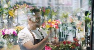 围裙改变的闭合的标志的男性卖花人打开在花店门微笑 股票录像