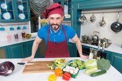 围裙的一个人在做素食主义者的厨房里沙拉 在家烹调准备的英俊的人沙拉在厨房里 英俊的愉快的男性 库存照片