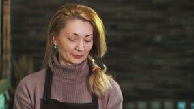 围裙的一个妇女卖花人,站立在花店的柜台后,看照相机,微笑 股票视频