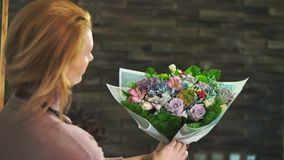 围裙的一个妇女卖花人,站立在花店的柜台,包裹一花束