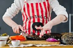 围裙的一个男孩烹调在厨房汉堡的 E r 免版税图库摄影