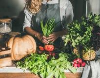 围裙的女性绿豆为切开在柜台做准备 免版税库存照片