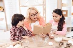 围裙的美丽的祖母,与她的孙一起,看菜谱在厨房里 免版税库存图片