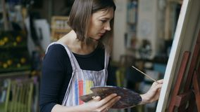 围裙绘画静物画图片的年轻画家女孩在艺术班的帆布