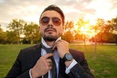固定他的英俊的年轻人领带 库存照片