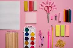 固定式概念、剪刀平的位置顶视图照片,铅笔,纸夹、计算器、稠粘的笔记、订书机和笔记薄在桃红色a 库存图片