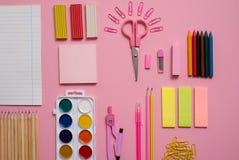 固定式概念、剪刀平的位置顶视图照片,铅笔,纸夹、计算器、稠粘的笔记、订书机和笔记薄在桃红色a 免版税库存照片