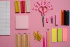 固定式概念、剪刀平的位置顶视图照片,铅笔,纸夹、计算器、稠粘的笔记、订书机和笔记薄在桃红色a 图库摄影