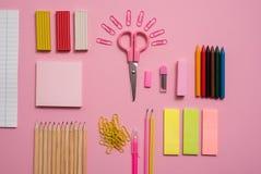固定式概念、剪刀平的位置顶视图照片,铅笔,纸夹、计算器、稠粘的笔记、订书机和笔记薄在桃红色a 免版税库存图片