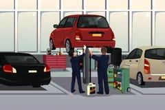 固定汽车的汽车机械师在敞篷下 免版税库存图片