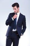 固定他的年轻典雅的商人领带 免版税图库摄影