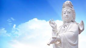 固岸yin慈悲雕象的女神有天空背景 图库摄影