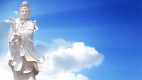 固岸yin慈悲雕象的女神有天空背景 免版税图库摄影