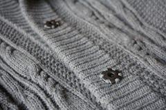 紧固羊毛毛线衣的灰色按钮细节  免版税库存照片