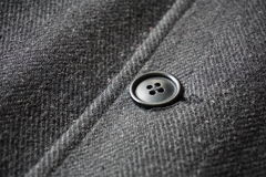 紧固鱼骨冬天外套的一个黑暗的按钮的细节 免版税库存照片