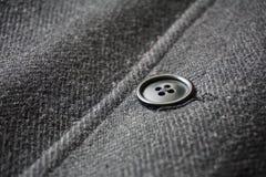 紧固鱼骨冬天外套的一个黑暗的按钮的细节 库存照片