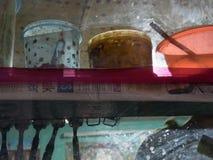 国内内部的抽象背景纹理:与罐和碗的一个架子由塑料制成,点燃与一个电灯泡,匙子 免版税库存照片
