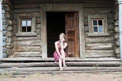 国家女孩坐一个老木房子的门廊 免版税库存照片