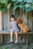 国家女孩坐与她的狗的一条长凳在藤下 木 图库摄影