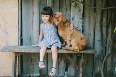 国家女孩坐与她的狗的一条长凳在藤下 木 免版税图库摄影