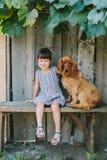 国家女孩坐与她的狗的一条长凳在藤下 木 库存照片